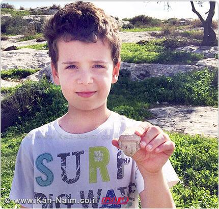 איתי הלפרין, בן ה-8 מהישוב פרדסיה שבשרון, עם ראש פסלון שנתגלה על ידו בתל בית שמש מתקופת בית ראשון