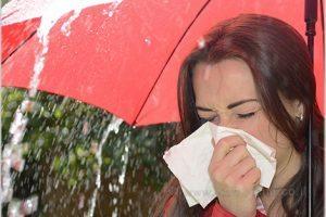 אישה עם מטרייה מקנחת את האף