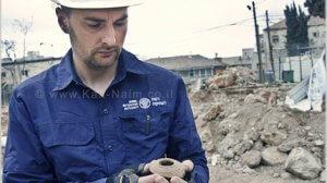 מנהל החפירה, אלכס ויגמן, מחזיק נר מהתקופה הרומית המאוחרת שנמצא באתר מתחם שנלר בירושלים | צילום: רשות העתיקות | עיבוד צילום: שולי סונגו ©