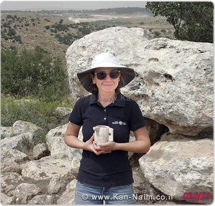 ארכיאולוגית רשות העתיקות, ג'ני מרכוס, מחזיקה ספל אבן מימי הבית השני שהתגלה בבית האחוזה במודיעין צילום: אברהם טנדלר