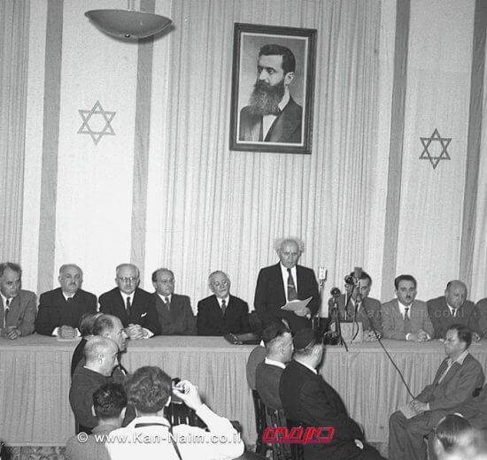 """ב-29 בנובמבר 1947 קיבלה עצרת האומות המאוחדות החלטה המחייבת הקמת מדינה יהודית בארץ-ישראל. מתוך בטחון בצור ישראל, הננו חותמים בחתימת ידינו לעדות על הכרזה זו. צילום: לע""""מ"""