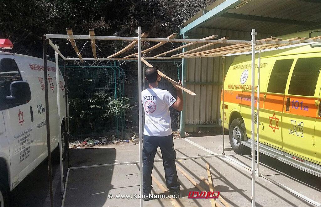 בניית סוכה בתחנת מגן דוד אדום בחניית אמבולנסים בעיר נתניה | צילום: דוברות מדא| עיבוד צילום: שולי סונגו ©