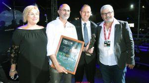 ראש העיר עכו, מר שמעון לנקרי, עם מנכל פסטיבל עכו מר אלברט בן שלוש מעניקים עיטור יקיר הפסטיבל למר ג׳קי בכר | עיבוד צילום: שולי סונגו ©