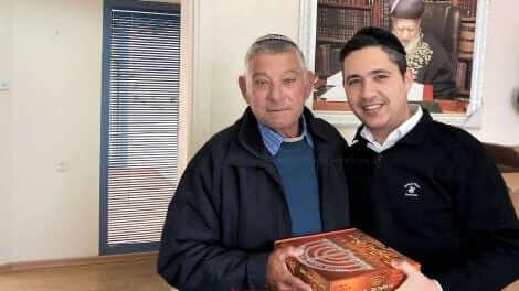 המשנה לראש עיריית חדרה, בועז ביטון, מעניק לגבאי בית כנסת בעיר ערכת שמן זית זך להדלקת נרות חנוכה