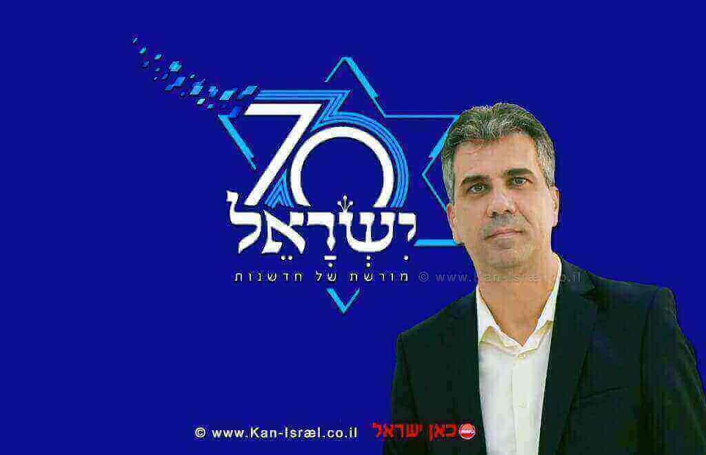 שר הכלכלה והתעשייה, מר אלי כהן ברקע: לוגו חגיגות ה-70 לעצמאות ישראל