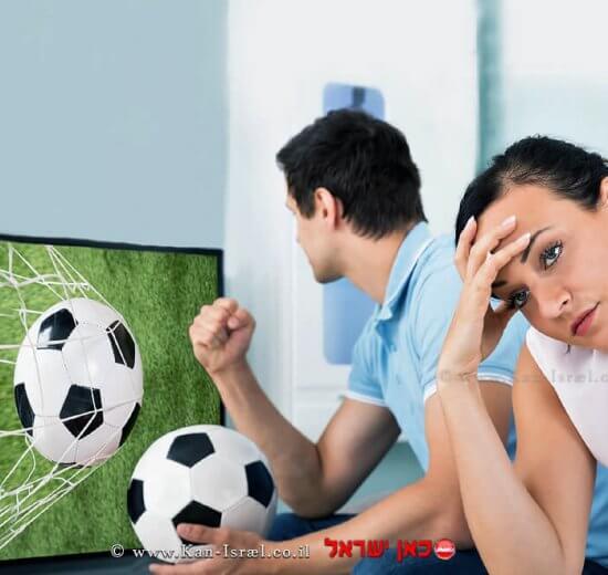 זוג צופה בטלוויזיה במשחק כדורגל