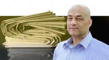 פרופ' צבי רייך ראש המחלקה לתקשורת באוניברסיטת בן-גוריון בנגב, ברקע: ערימת עיתונים | עיבוד צילום: שולי סונגו