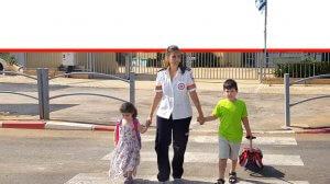 אשת צוות מגן דוד אדום עם שני תלמידי כיתה א' חוצים את הכביש בביטחה | צילום: דוברות מדא | עיבוד צילום ממחושב: שולי סונגו©