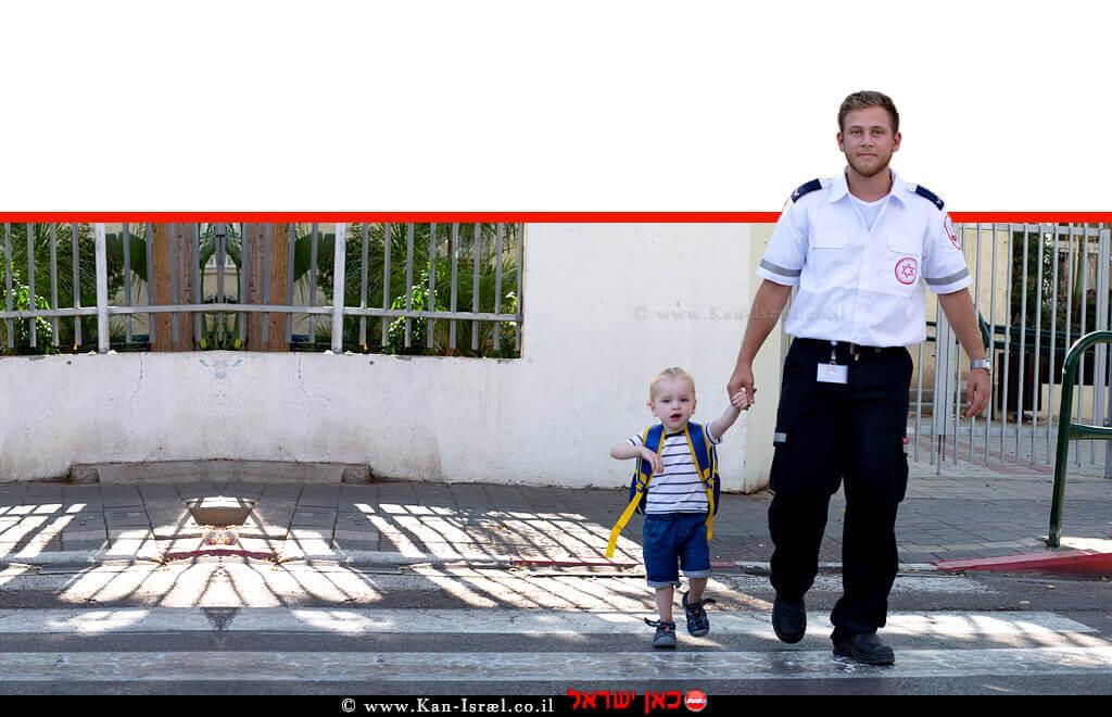 פראמדיק מדא עם ילד תלמיד כיתה א' חוצים את הכביש בביטחה | צילום: דוברות מדא