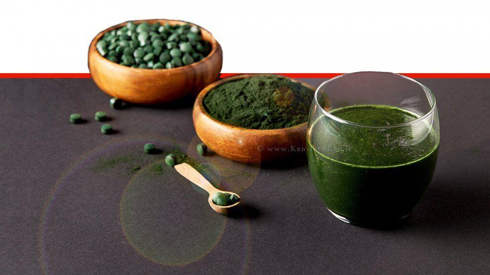 אבקת אצות ספירולינה - כף עץ מסודרת, כוס שייק טרי מספירולינה, קערות עם אבקת ספירולינה וכדורי ספירולינה על שולחן אפור | עיבוד צילום ממחושב: שולי סונגו©