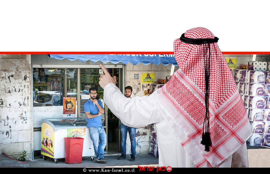 איש מוסלמי מצביע באצבע ברקע: שני גברים עומדים בסופרמרקט מכולת באזור העיר העתיקה של בירושלים | עיבוד ממחושב: שולי סונגו©