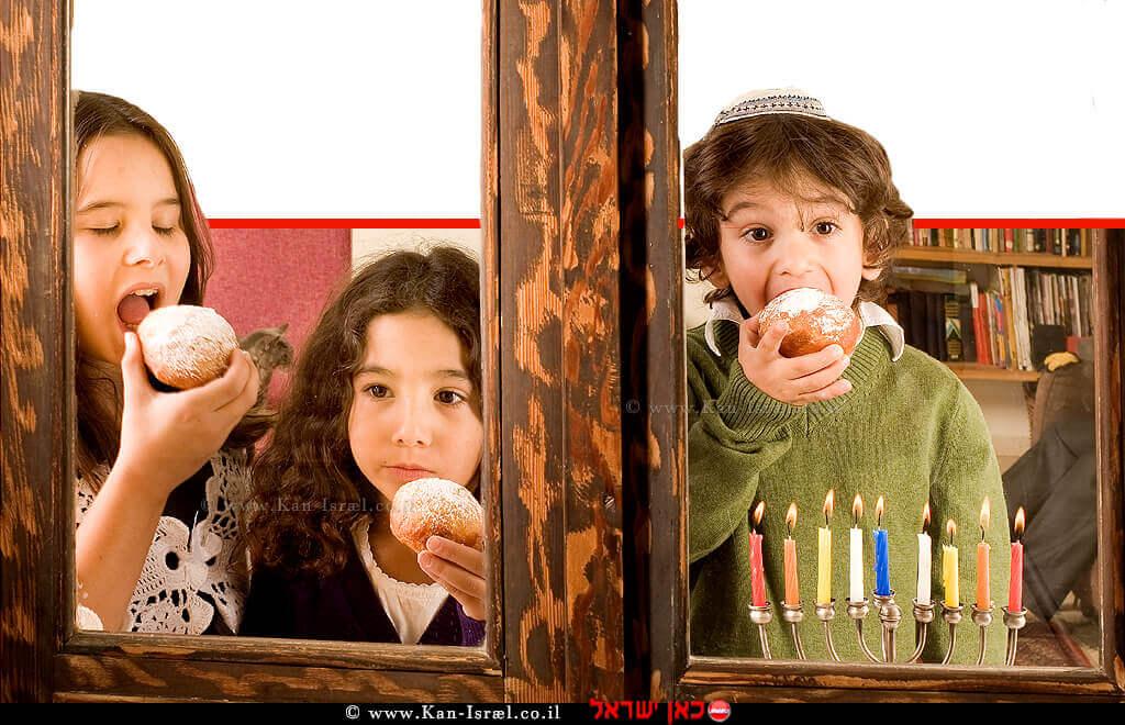 ילדים אוכלים סופגנייה עם חנוכייה דולקת עם נרות חנוכה | עיבוד ממחושב: שולי סונגו©