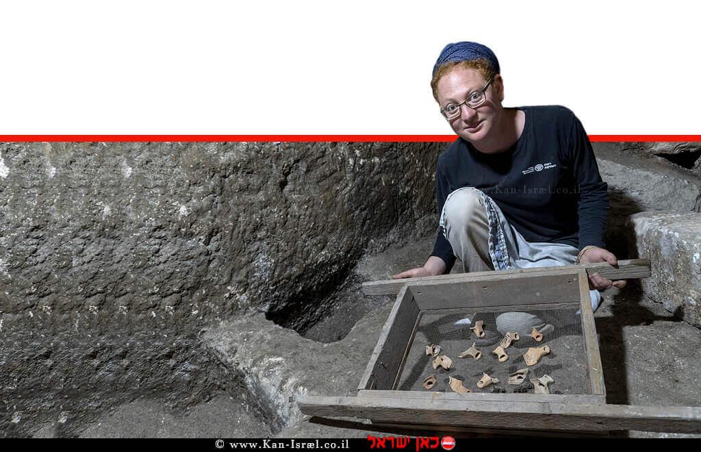 תהילה שדיאל מנהלת החפירה, עם שברי נרות חרס מתקופת בית שני שנחשפו בתוך המערכת התת קרקעית | צילום: שי הלוי, רשות העתיקות | עיבוד צילום: שולי סונגו ©