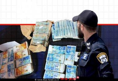 הכסף שנתפס אצל חלפן כספים בעיר כפר קאסם, הדמיית שוטר מביט בכסף הרב | צילום: דוברות המשטרה | עיבוד: שולי סונגו ©