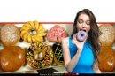 צעירה אוכלת סופגנית חישוק (דונט) ברקע: סופגניות חישוק (דונטאס) בציפוי פריך ובמילוי קרם | צילום ויקיפדיה | עיבוד צילום: שולי סונגו ©