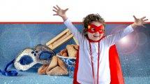תלמיד כיתה א' מחופש בתחפושת לחג פורים ברקע: משלוח מנות של אוזני המן ורעשן |עיבוד צילום: שולי סונגו ©